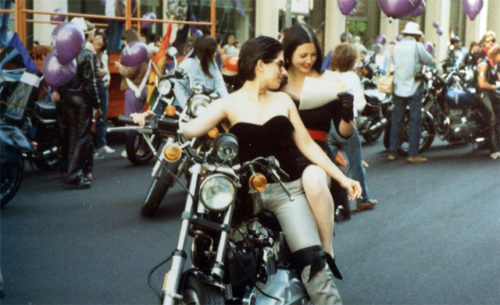 A lesbian couple shares a moment aboard a motorcycle before the 1983 Pride Parade in San Francisco.