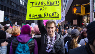"An unidentified man holds a sign that reads ""Trans Rights Are Human Rights"" at the Women's March on New York City on January 21, 2017 in New York."