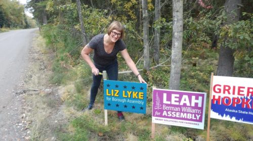 Liz Lyke poses with a yard sign.