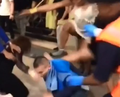 A woman's leg is stomping on someone on the ground while a crowd watches