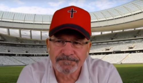 A man in a red cap with a cross. The background is a computer generated image of a stadium.