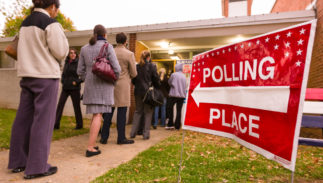 ARLINGTON, VIRGINIA, USA - NOVEMBER 4, 2008: Voting polling place sign and people lined up on presidential election day.