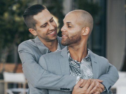 Two men in gray suits hugging