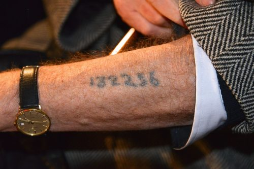 A Holocaust survivor displaying his arm tattoo.