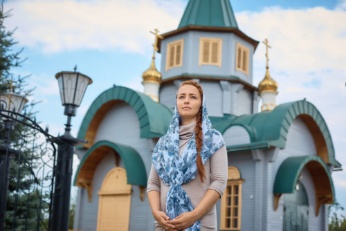 A Russian woman stands in front of a small wooden church.