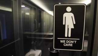 """A bathroom with a """"We don't care"""" sign on it that has a bi-gender stick figure."""