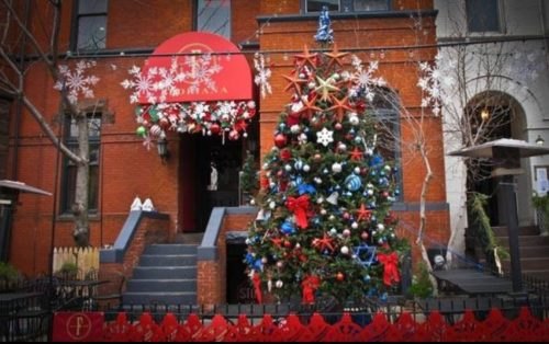 A Christmas tree in front of a red brick building.