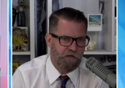 Gavin McInnes in a white shirt and a red tie, talking into a microphone