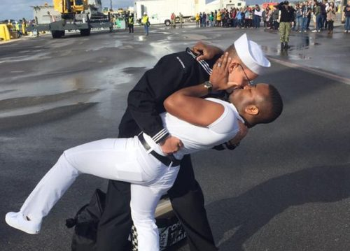 Two men kissing, one is a sailor.
