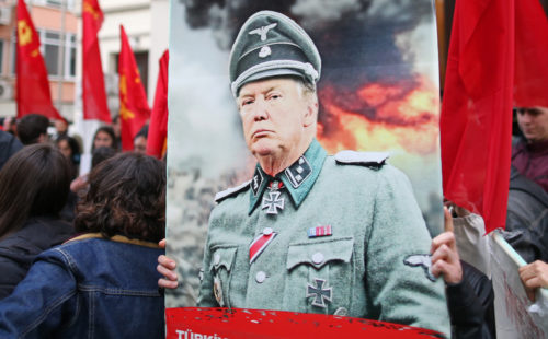 ISTANBUL, TURKEY, 14 APRIL 2018. A protestor hold picture of US President Donald J. Trump with Nazi uniform during a protest against the United States.