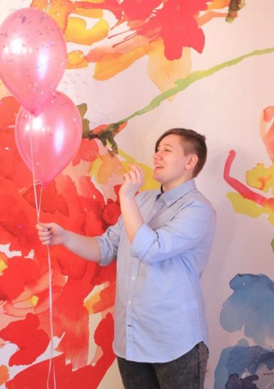 Adrian popping pink balloons