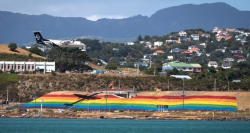 The giant rainbow flag with Wellington in the background and the shadow of an airplane