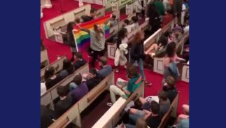 Students walking out holding a rainbow flag