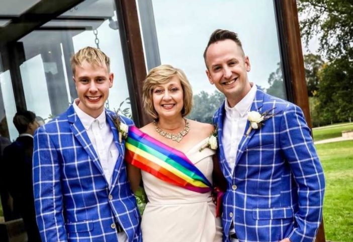 Vanessa Hall, her son, and his husband. The men are in blue suits and she is wearing the rainbow sash