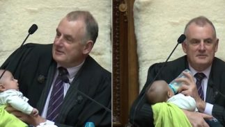 NZ Parliament Speaker Trevor Ballard holds 1-month-old Tutanekai Smith-Coffey, the son of MP Tamati Coffey and his husband, Tim Smith.