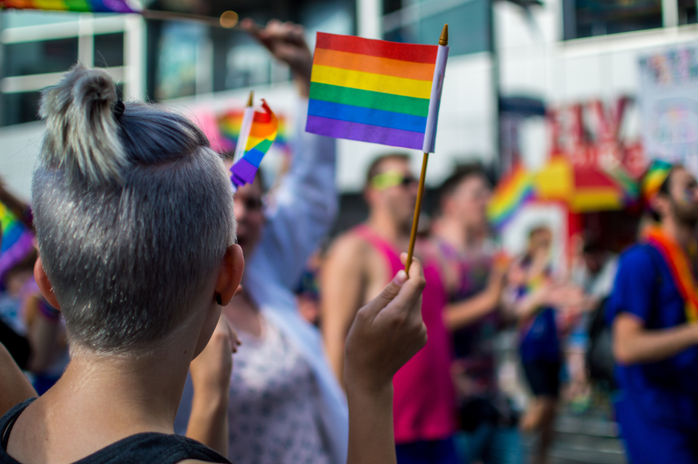 A woman with a buzzcut waving a small rainbow LGBT, or Queer, pride flag at a march.