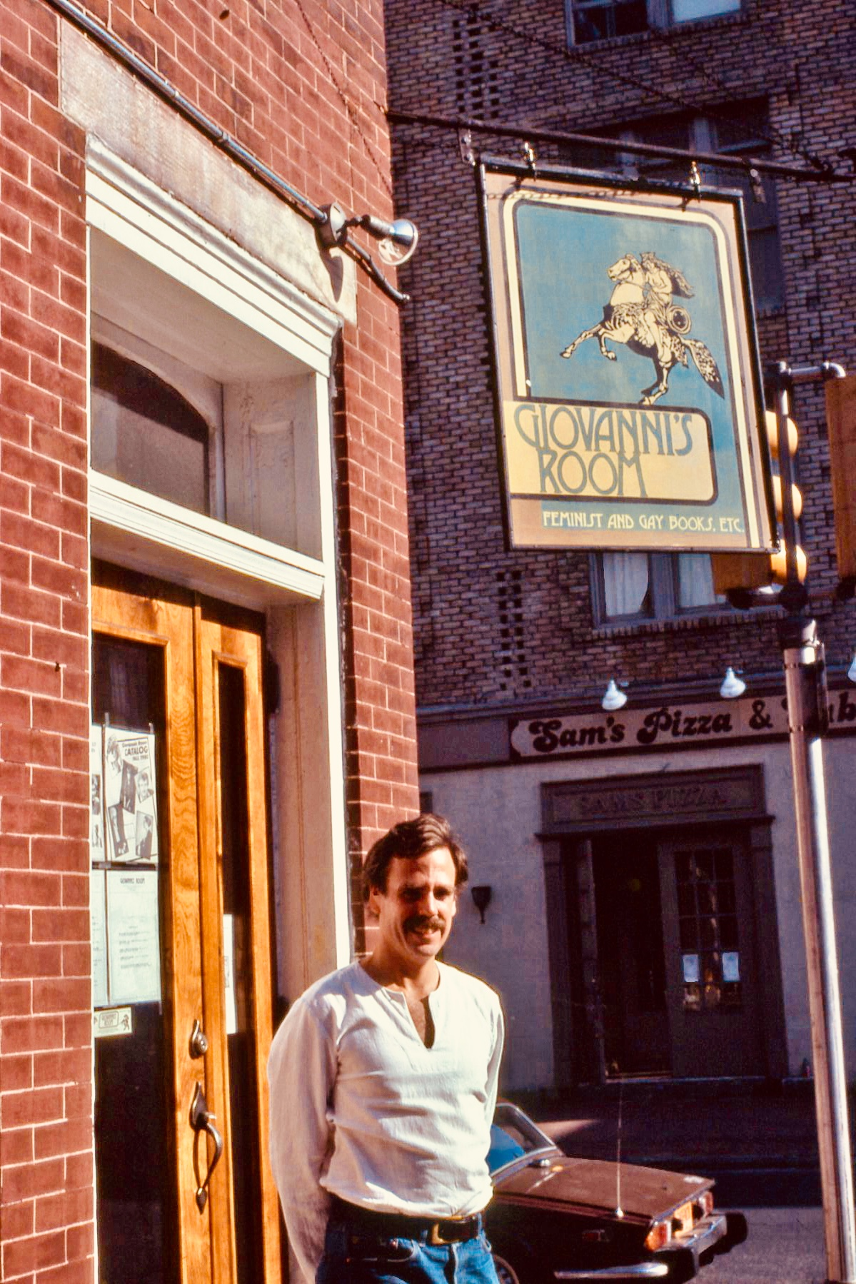 Ed Hermance standing in front of Giovanni's Room in the 1980s.