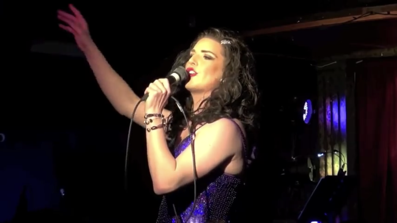UK Cabaret entertainer Topsie Redfern singing into a microphone on a stage.