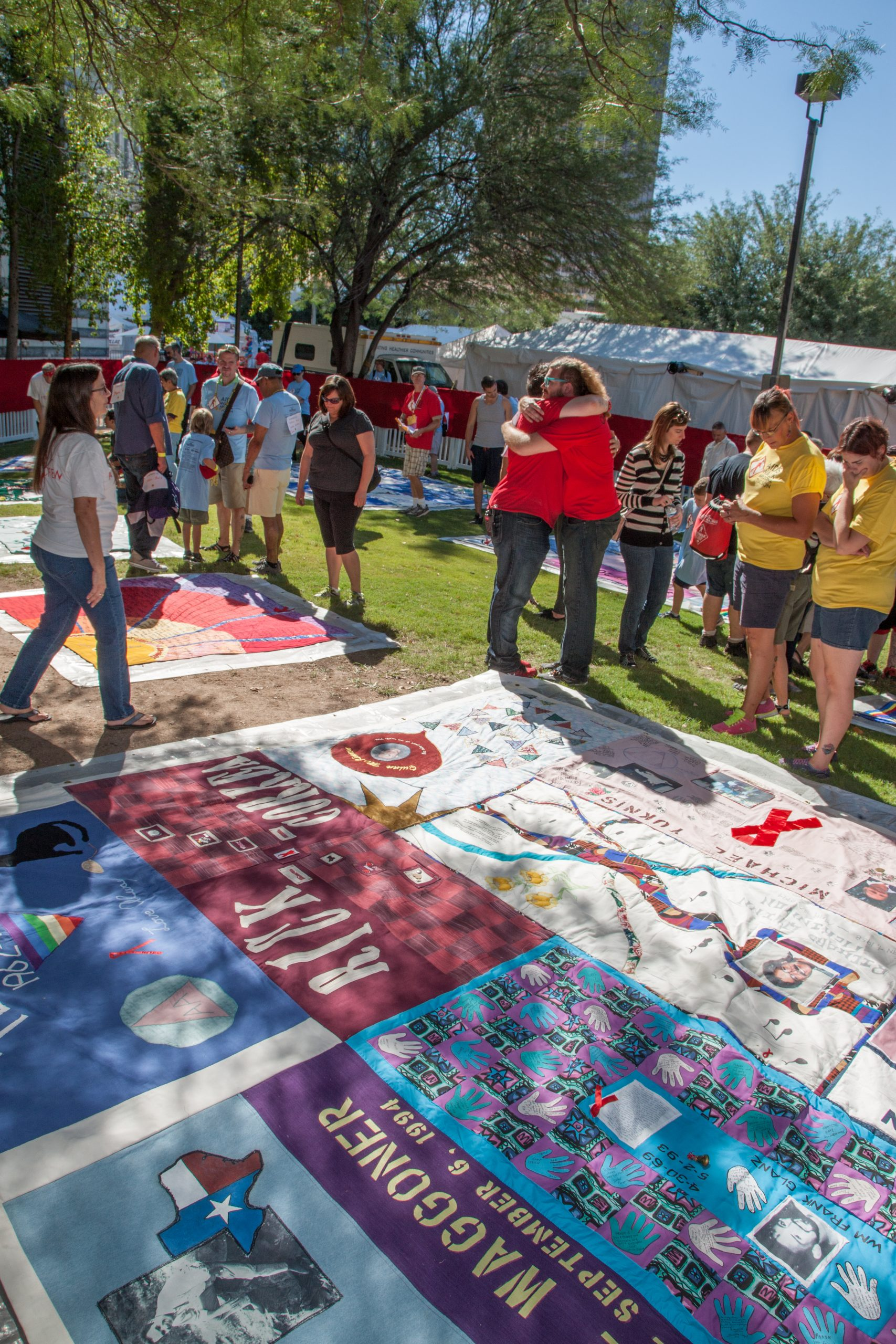 Unidentifed people hugging near section of AIDS Quilt on October 12, 2014 in Tucson, Arizona, USA