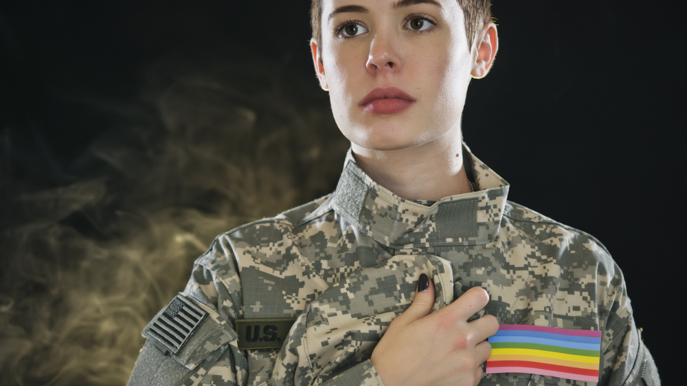 A queer soldier with a Pride flag on her uniform touches her heart.