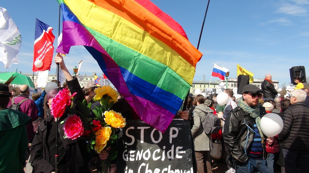 "Protestors with a rainbow flag and a sign that says ""Stop genocide in Chechnya"""