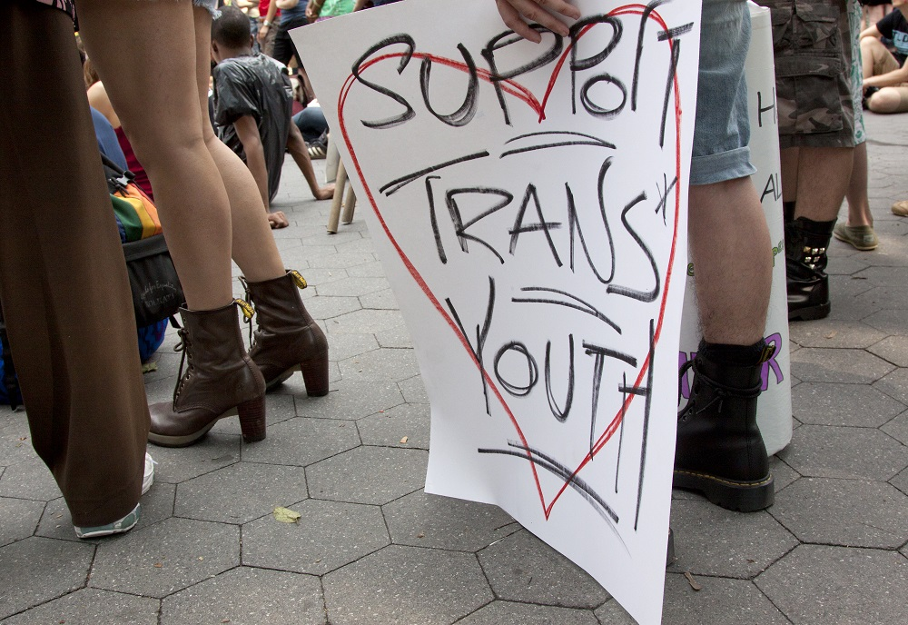 ": A supporter holds a sign that says ""Support Trans Youth"""