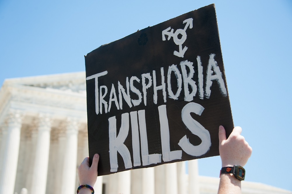 JUNE 25: A sign denouncing transphobia is held up in front of the U.S. Supreme Court at the March for Marriage in Washington, DC on June 25, 2016.