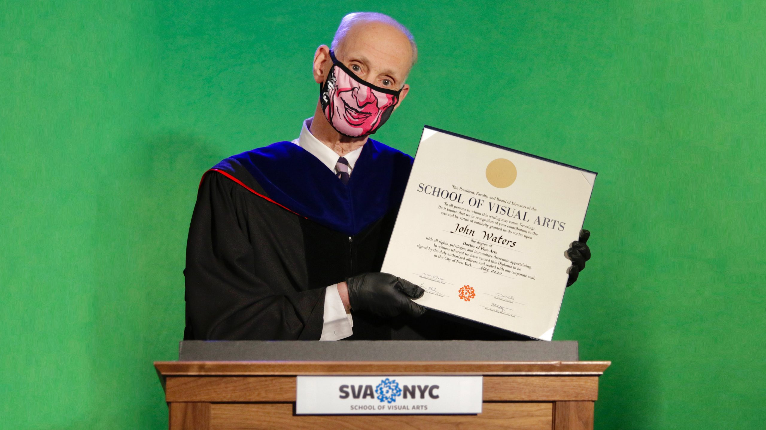 John Waters poses with his honorary degree wearing a mask