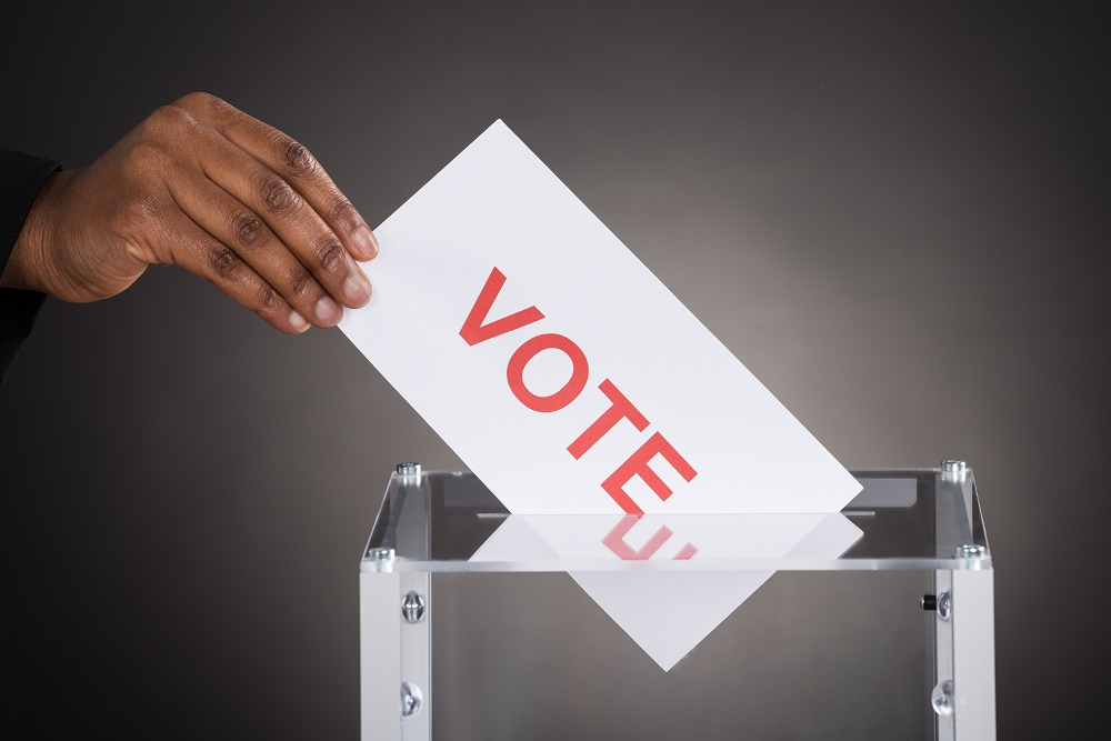 """A hand putting a card marked """"vote"""" into a ballot box"""