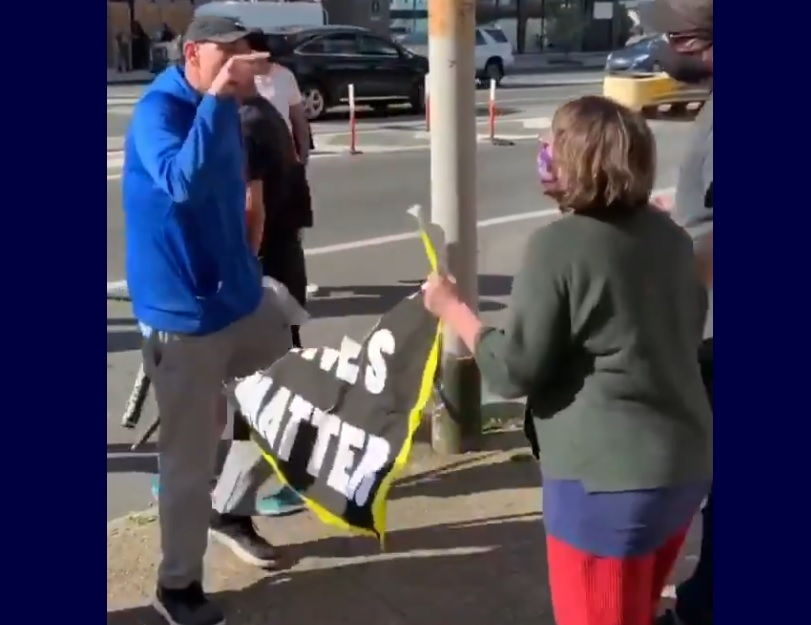 """A man in a blue sweater pointing at a protestor with half a sign that formerly said """"black lives matter"""""""