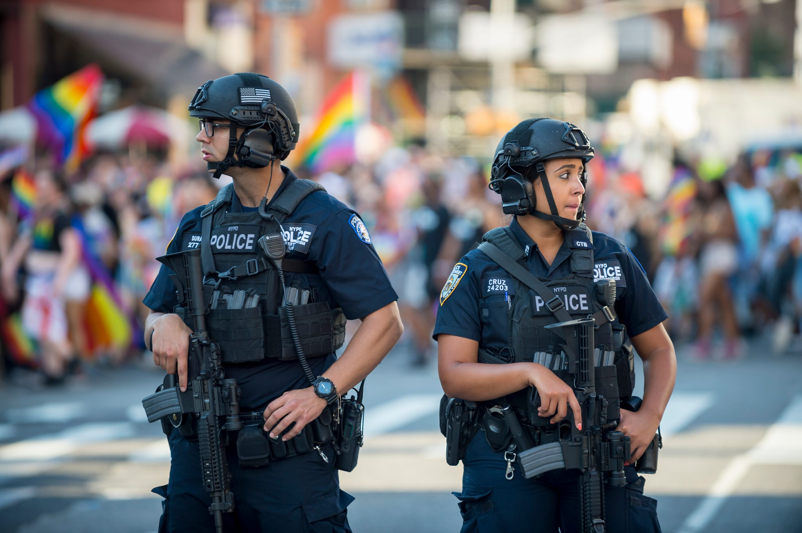JUNE 25, 2017: NYPD police officers stand with hands on their weapons, providing security on the sidelines of the annual Gay Pride parade as it passes through Greenwich Village.