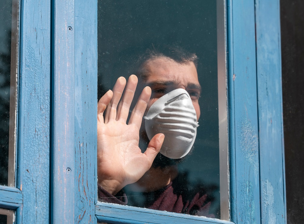 A person with a facemask pressing their hand against a window. They want out, y'all.