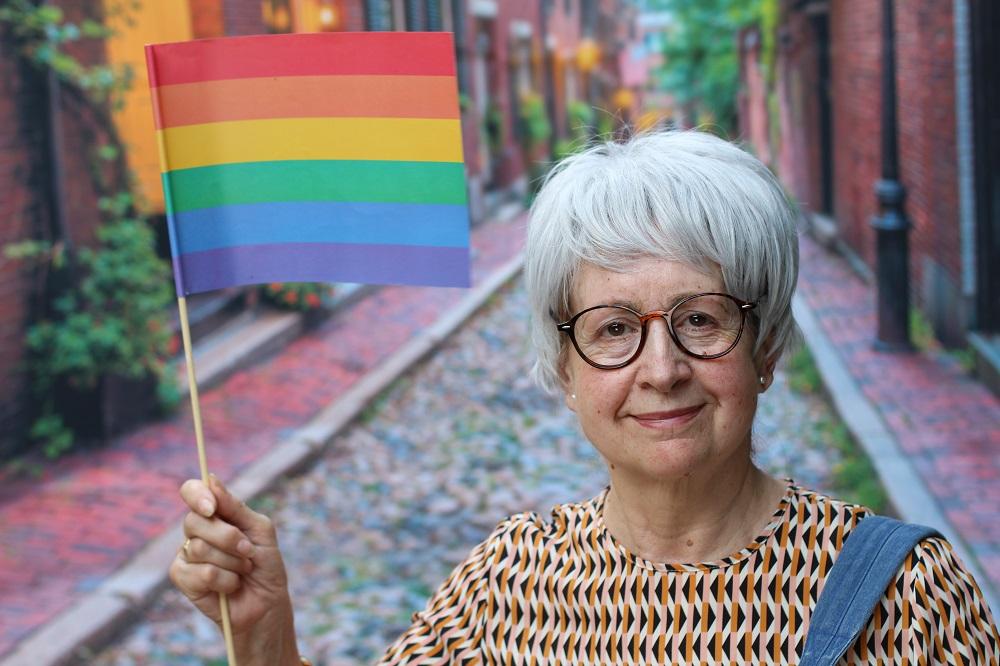An older woman with a rainbow flag