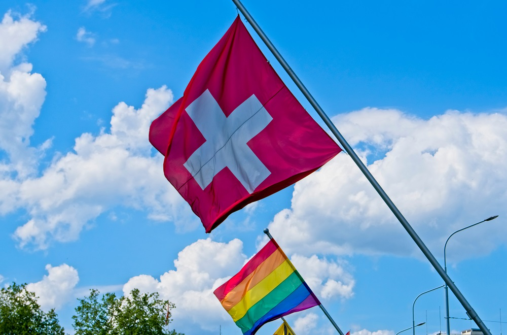 Swiss and rainbow flags fly on a bridge in Geneva