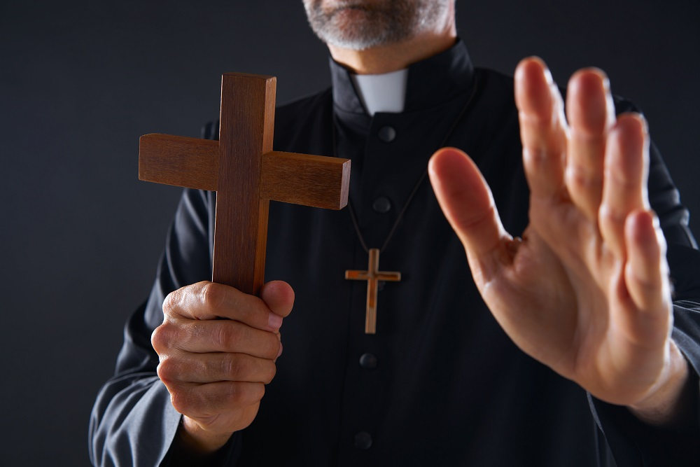 A Catholic priest doing an exorcism... I mean, it's obviously a stock photo and the priest is kinda hot and he's holding a wooden cross, although you can't really see his face. And he's not a priest, he's just a model.