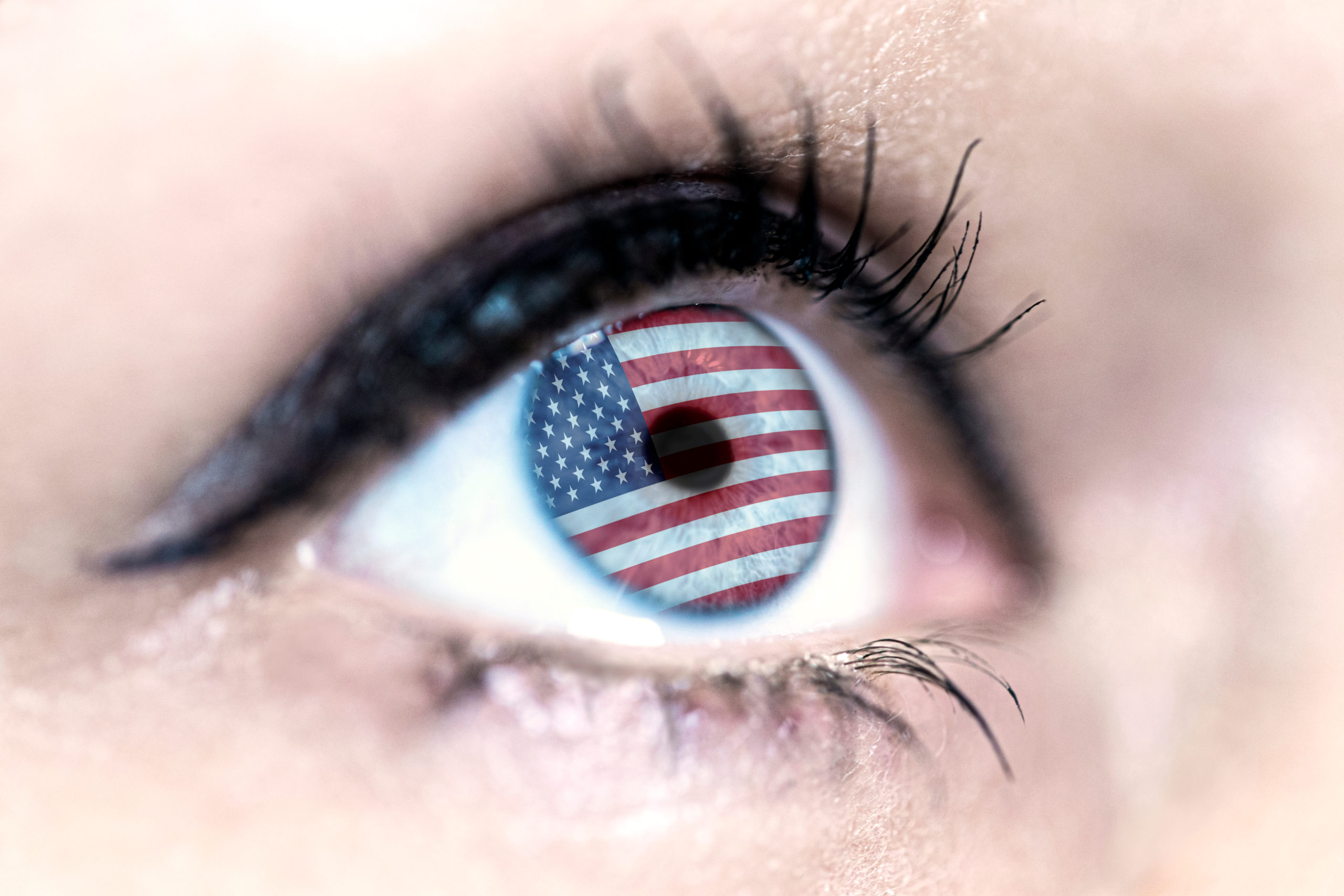 woman blue eye in close up with the flag of USA n in iris with wind motion. video concept