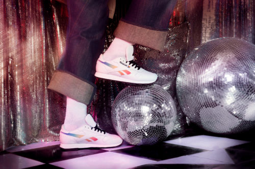 Model wearing Reebok Pride Club C sneakers while stepping on a disco ball
