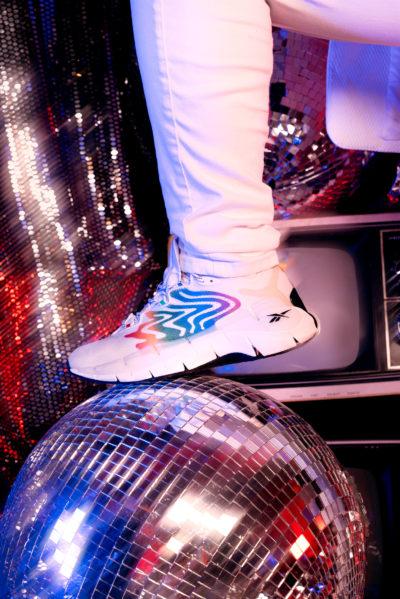 Model wearing Reebok Zig Kinetica II sneakers while stepping on disco ball