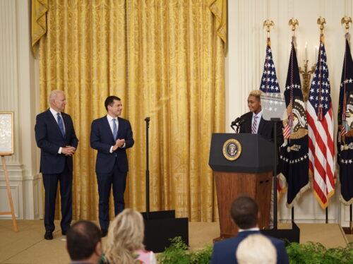 President Joe Biden (left) and Transportation Secretary Pete Buttigieg applaud 16 year-old Ashton Mota as Mota speaks to the crowd assembled in the White House East Room