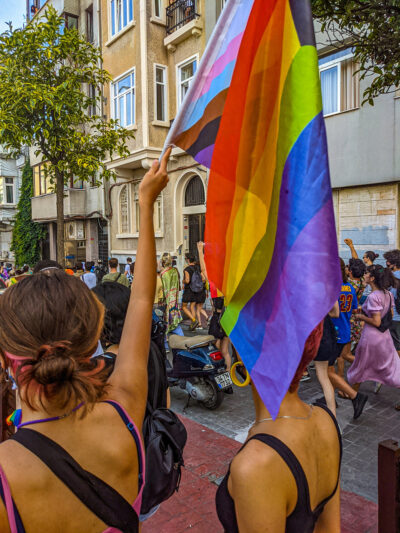 Two women, with one holding up a Progress Pride flag, during an unsanctioned march recognizing Pride in Istanbul, Turkey on June 17, 2021.