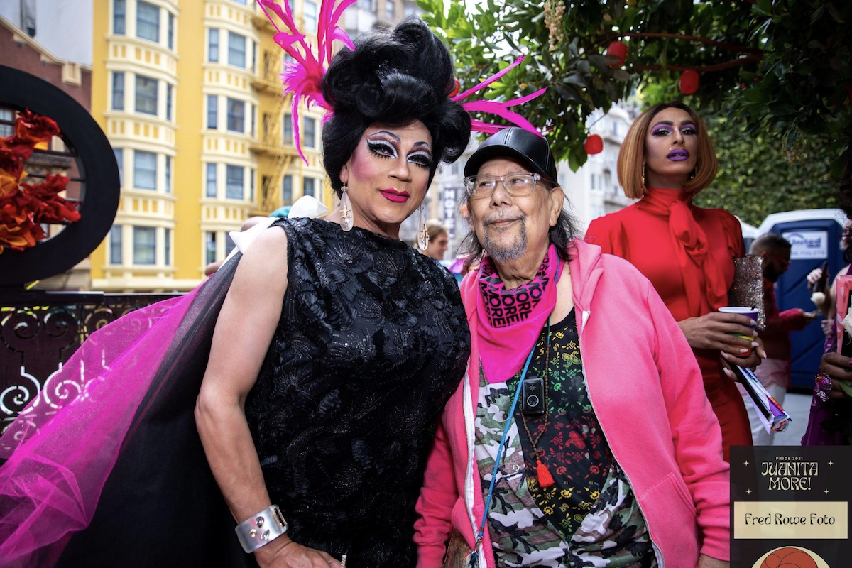 """Juanita More with her neighbor Eduardo at her annual Pride fundraising party in 2021. """"He is one of the elders I look after,"""" Juanita said. """"We met six years ago. He told me 'Juanita, I don't know why it took so long in my life to meet you.'"""""""